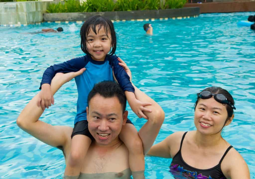 father with his child and mother learning swimming